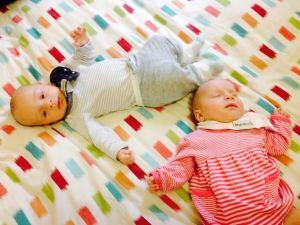 Bebés gemelos jugando en la cama